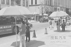 """凉伞站岗 解决炎夏等车""""热问题""""(图)"""