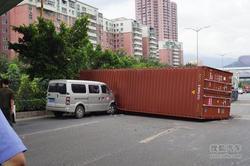 货柜车立交桥上转弯货箱滚落 砸中面包车